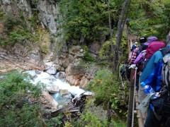 十字峡吊橋を待つ登山者、下は剱沢