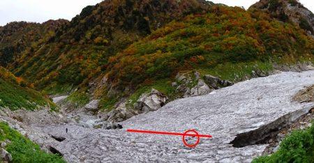 高巻き道から見た雪渓。赤線の下が空洞で赤丸印のところで穴が開き始めている。