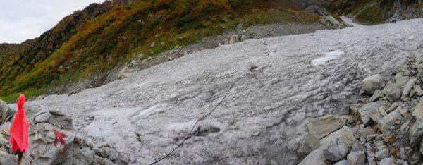 ピンクの旗と黒いパイプが目印の長次郎谷出合下の雪渓取り付き地点。右上が剱沢本流