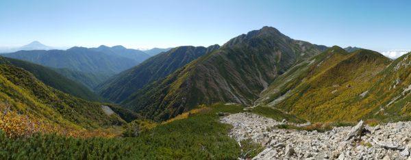 荒川前岳からの下り道、正面に赤石岳、左手に富士山を眺めながらの快適な縦走路。右手中ほどにはダケカンバに囲まれた荒川小屋(2014/09/27)