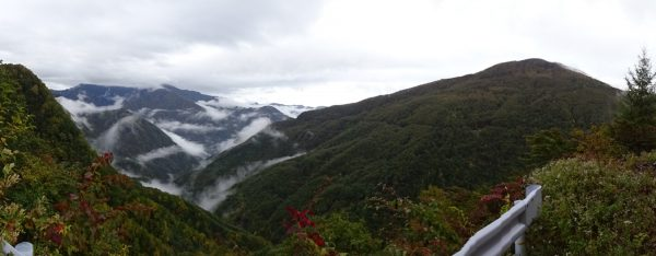 鳥倉林道で見る山深い景色。右の山の山腹に見える白い横線の位置がゲート口駐車場
