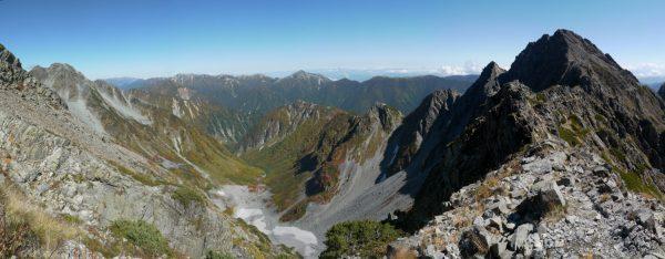 吊尾根にて、前穂高岳と北穂高岳に囲まれて深く沈む涸沢カール。その底に小さく涸沢ヒュッテが見える。