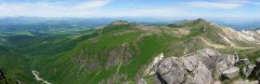 久住山山頂にて瀬の本高原の先の阿蘇山から台地状の肥前が城、その向こうに扇が鼻、星生山にかけてのパノラマ。右に少し噴煙の上がる硫黄山。